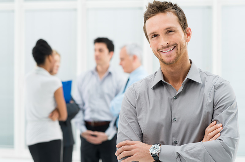 Portrait Of Young Handsome Businessman Smiling In Office